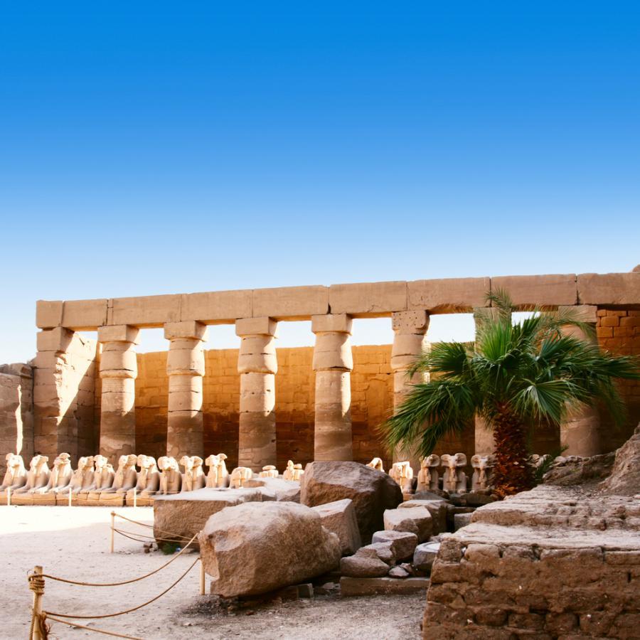 """Karnak w Egipcie. W Karnaku znajduje się zespół świątyń wzniesionych w różnym czasie, poświęconych bogom tebańskim. Centralne miejsce zajmuje największa na świecie świątynia z salą kolumnową, tzw. """"Wielki Hypostyl"""" – świątynia Amona-Re. Od północy przylega do niej świątynia Montu – boga wojny, a na południe położone jest sanktuarium bogini Mut, żony Amona. Świątynie te są połączone ze sobą alejami procesyjnymi. W 1979 Karnak został wpisany na Listę światowego dziedzictwa UNESCO."""