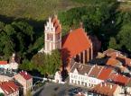 <strong>Jeziorany</strong> <br></br> Założycielem Jezioran był biskup warmiński Herman z Pragi, który położył duże zasługi przy uregulowaniu granic biskupstwa i dominium warmińskiego oraz zasiedleniu południowej Warmii. W zastępstwie biskupa przywilej lokacyjny na prawie chełmińskim wystawił w 1338 roku kanonik braniewski Mikołaj i wójt biskupi Henryk von Luter. Zasadźcą został Henryk Wandepfaffe. Miastu przydzielono 110 włók ziemi, z tego 11 włók należało do sołtysa, 6 stanowiło uposażenie kościoła, jedną zarezerwowano jako pastwisko na potrzeby zamku, jedną przeznaczono na zabudowę miasta. Murowany zamek biskupów warmińskich wybudowano po 1350 r. Była to budowla siostrzana do zamku w Reszlu, dwuskrzydłowa z narożną wieżą typu bergfried, poprzedzona od wschodu małym przedzamczem. Zamek rozebrano po pożarze w 1783 r., a materiał przeznaczono na odbudowę miasta. Zachowała się jedynie dolna część głównego skrzydła zachodniego ze sklepionymi piwnicami. Mury obronne miały trzy bramy: Mostową, Młyńska i reszelską, zostały wzniesione po 1360 r. Pożar z 1783 r. zniszczył Jeziorany niemal doszczętnie. Odbudowano je w całości murowane, co na owe czasy było niezwykłe. Wspominał nawet o tym biskup Ignacy Krasicki. <br></br> Fot. ZeroJeden / Wikimedia Commons, lic. cc-by-sa