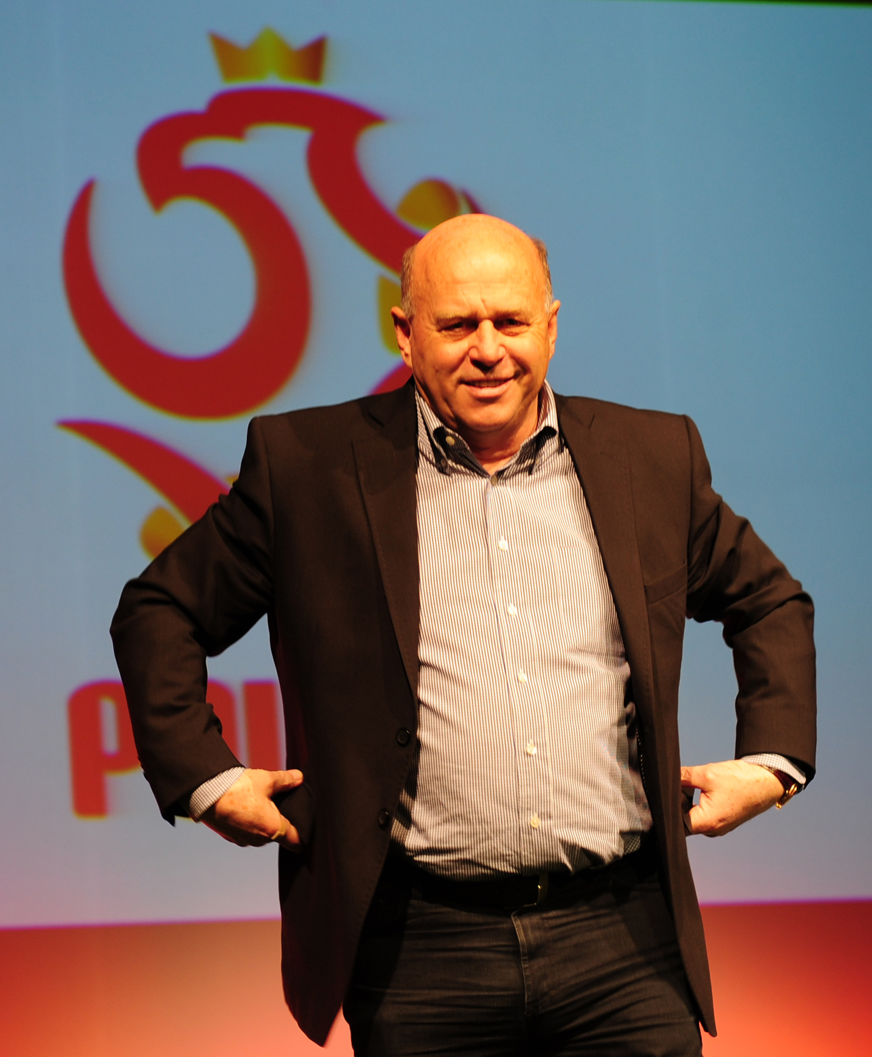 Prezes PZPN Grzegorz Lato na tle nowego logo Związku